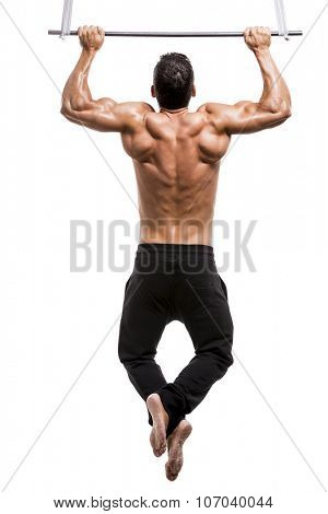 Muscle man in studio making elevations, isolated over a white background