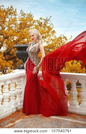 Sexy Young Beauty Woman In Fluttering Red Dress. Elegant Slim Lady Posing On The Balcony With Balust