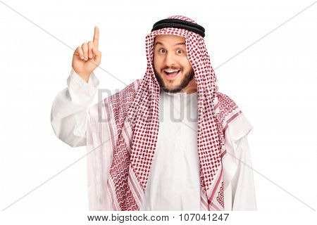 Young male Arab with a checkered veil pointing up with his finger and looking at the camera isolated on white background