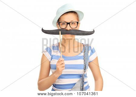 Young blond girl holding fake mustache on her face and looking at the camera isolated on white background