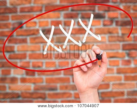 Man Hand writing XXX with black marker on visual screen.