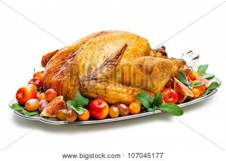 Garnished roasted turkey on platter over white background