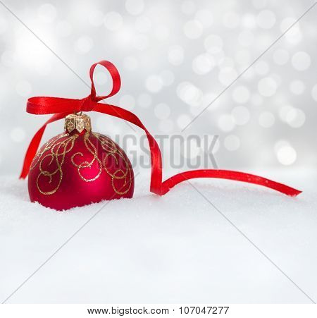 Christmas ball with ribbon on snow