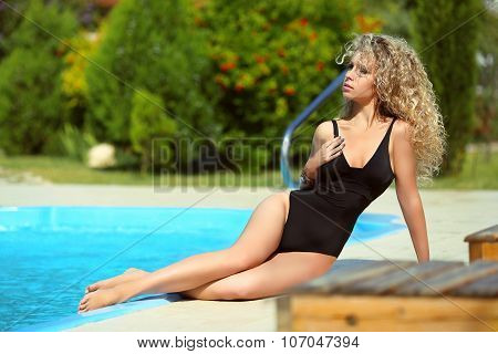 Wellness Body. Beautiful Sensual Woman Model In Black Bikini Posing And Tanned By The Blue Swimming