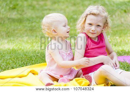 little girls sitting on blanket