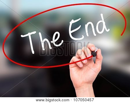 Man Hand writing The End with black marker on visual screen.