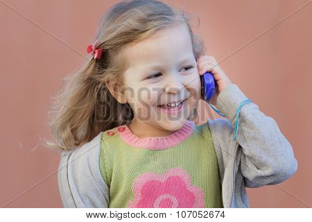 Preschooler Blonde Girl Having Fun During Her Dialogue By Mobile Phone