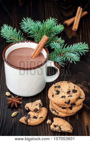 Spicy hot chocolate with cinnamon stick and chocolate chip cookies over dark wooden background.