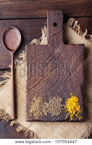 Wooden cutting board and spoon with spices: cumin, carry, turmeric.