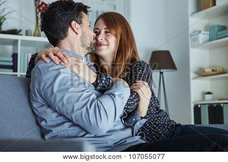 Young Happy Couple Hug On Sofa