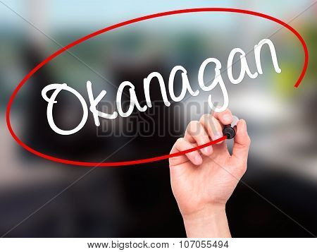 Man Hand writing Okanagan with black marker on visual screen