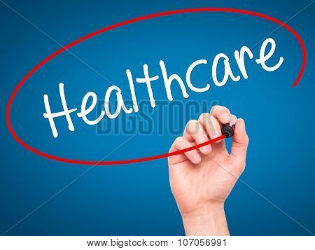 Man Hand writing Healthcare with black marker on visual screen