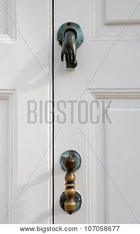 White door with a hand as doorknob