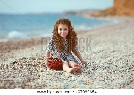 Funny Little Girl With Long Curly Hair Resting On The Beach. Outdoor Portrait.