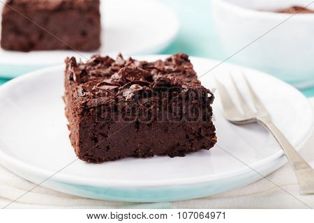Chocolate brownie, cake, white plate on a turquoise wooden background