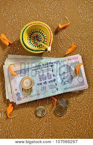 Hundred rupee notes and coins and traditional oil lamp. Banknotes are worshipped during festival of Diwali in India.
