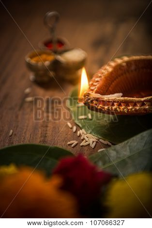 Indian decorative traditional clay lamp burning in the pooja set up. Selective focus treatment