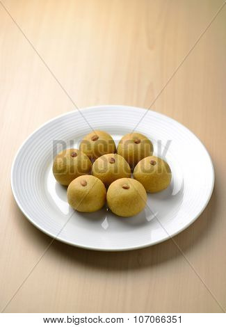 Indian home made sweet recipe- Rawa Ladoo arranged on white plate.