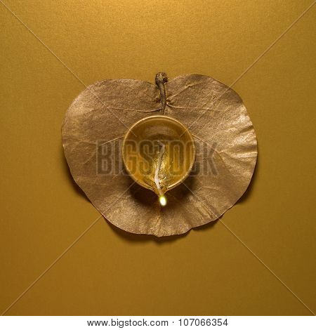 Earthen oil lamp on golden dry leaf. view from above. Indian religious background.