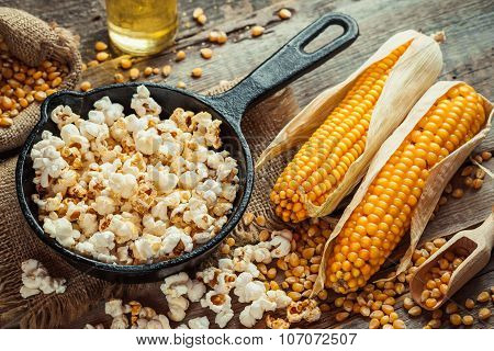 Prepared Popcorn In Frying Pan, Corn Seeds In Bowl And Corncobs On Kitchen Table.