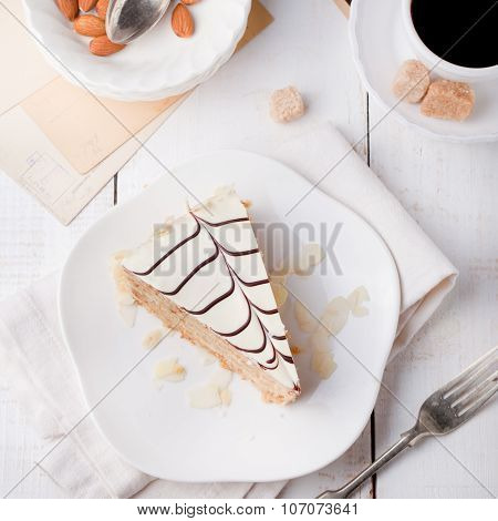 Traditional Hungarian Esterhazy cake with coffee cup and vintage postcards .