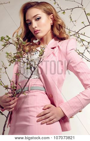 Gorgeous Young Woman With Blond Curly Hair Wears Elegant Suit And Bijou