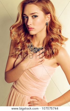 Young Woman With Blond Curly Hair Wears Elegant Dress And Bijou