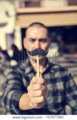 a young caucasian man holding a fake moustache in a stick in front of his face