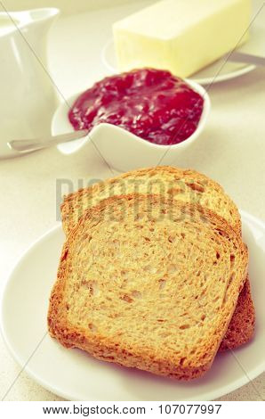 a set table with different plates with toasts, strawberry jam and butter