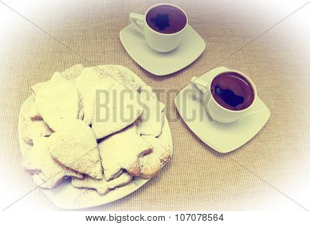 two cups of coffee with cookies on sac