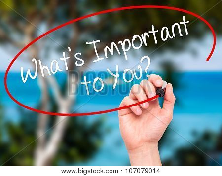 Man Hand writing What's Important to You? with black marker on visual screen.