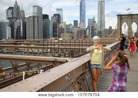 NEW YORK, USA - SEP 08, 2014: Girl takes pictures mother (with model release) on the walking part of the Brooklyn Bridge