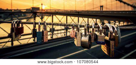 NEW YORK - JULY 11 2015: Love locks on the Brooklyn Bridge New York with sunrise in the background.