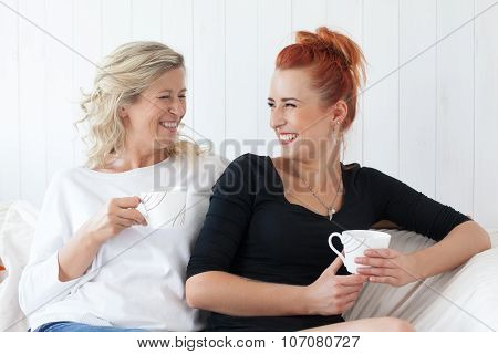 Two beautiful women-a mother and daughter sitting on the sofa at home, snuggled.