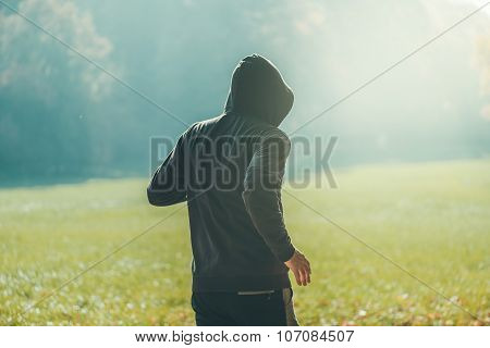 Hooded Man Jogging In The Park In Early Autumn Morning