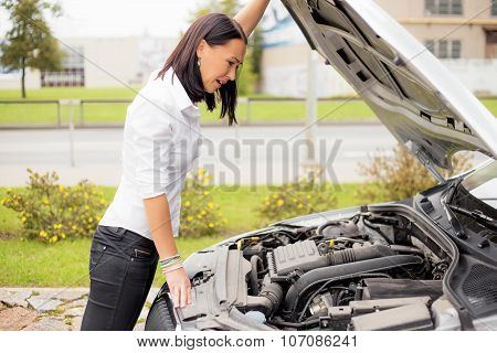 Woman looking at broken cars motor