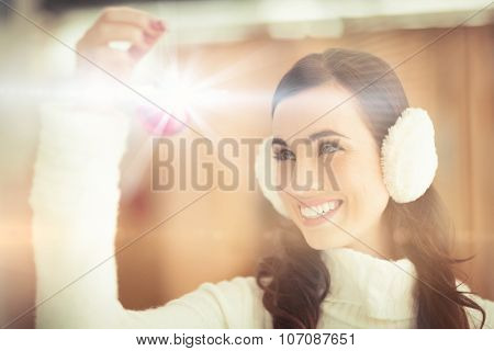 Pretty brunette with ear muffs holding bauble at home