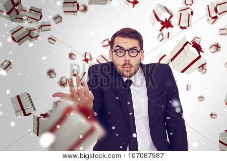 Doubtful businessman with glasses gesturing against snow