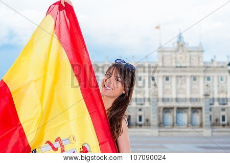 Young woman holding a flag in front of face.