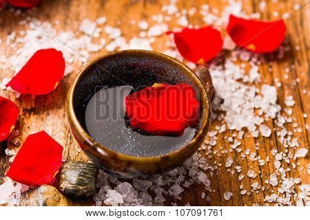 rose petals with bowl with pile of salt on old wooden board