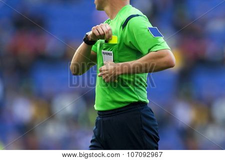 Soccer referee to point out a yellow card to a player during a match