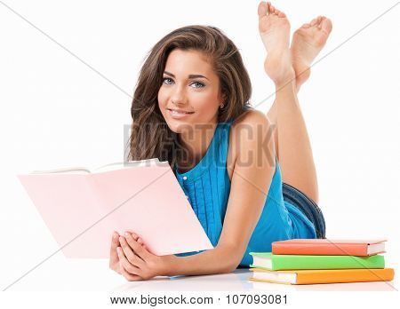 Beautiful student girl with books lying on floor, isolated on white background