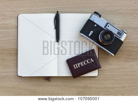 Notepad with pen, film camera and Press ID (inscription in Russian: PRESS) lying on a wooden table, top view with place for your text.