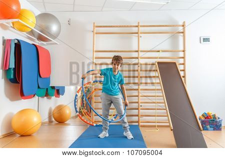 Young boy performs exercises with hula hoop in the gym.