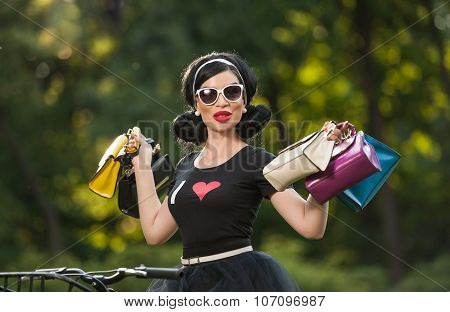 Woman with sunglasses holding purses against a green forest background. Portrait of young girl