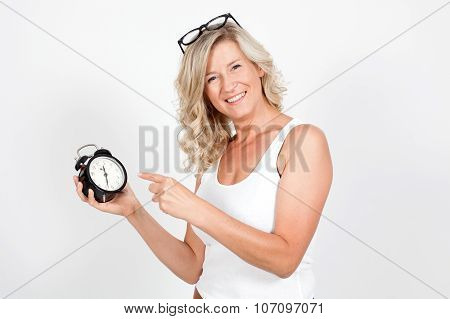 Beautiful blonde adult woman holding a clock, alarm clock. time, haste, punctuality, I'm late. It's
