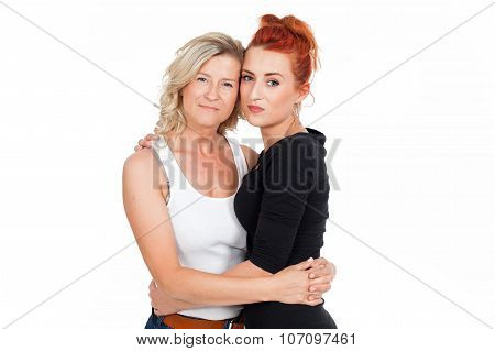 Two young, smiling, adult women - mother and daughter huddled together. Together., over white