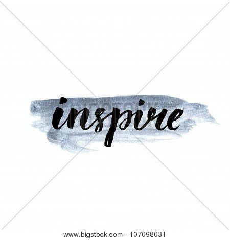 Inspire.  Calligraphy word handwritten on silver paint. Inspirational quote, brush lettering for car