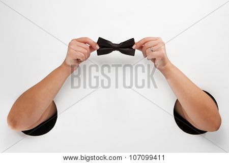 Female  hands through the holes on a white background are holding a black silk bow-tie