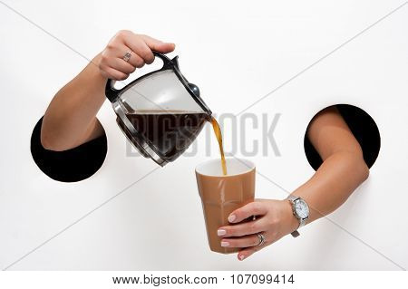 Female  hands through the holes on a white background pour coffee from coffee pot into a cup